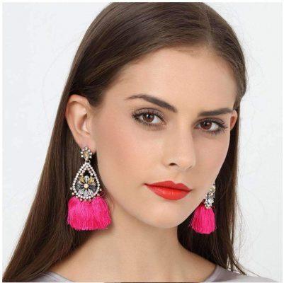 mujer con aretes de borlas rosa